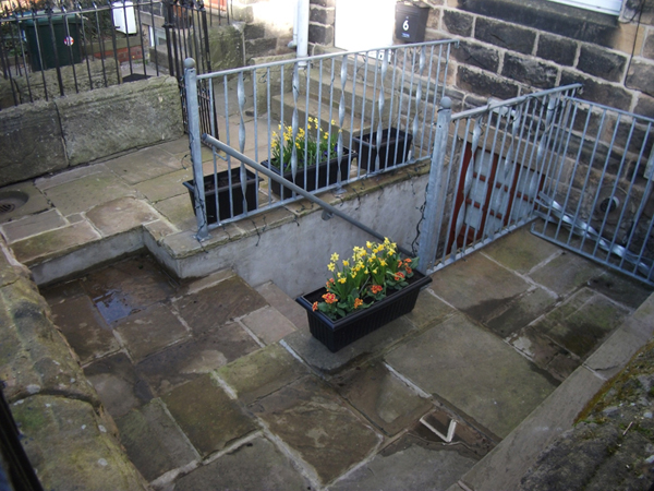 Steps down to basement kitchen formed by digging out gardens and knocking existing window into a doorway. Garden re flagged using traditional Yorkshire stone flags.