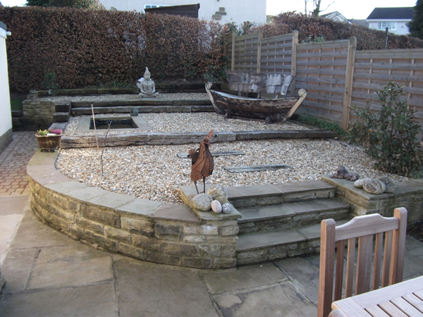 Japanese style raised level garden with small pond and railway sleeper steps.