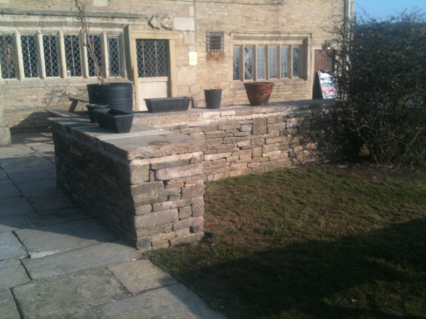 Random stone garden wall for planting beds.